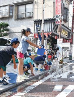 打ち水を楽しむ子どもたち