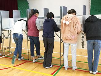 記載台で投票先を書き込む児童ら