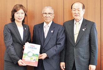 絵本を手渡す松井さん(中央)。左は平岩教育長、右は縁を作った最上さん