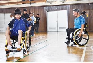 車いすの操作方法を指導する花岡さん(右)