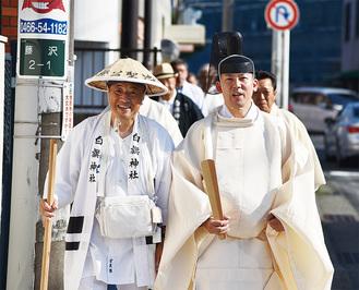 白旗神社まで最後の道のりを歩く小峯さん(左)と鈴木宮司ら