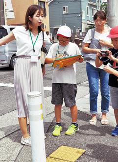 通学路を歩き、危険個所の写真を撮り、メモをとる児童ら
