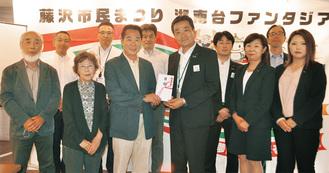砂永支社長(中央右)から寄贈を受けた北村会長(中央左)