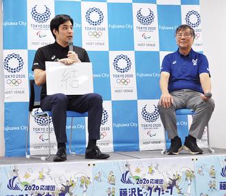 市役所で開かれた公開記者会見で五輪開催の抱負を「結」と紹介する元競泳選手の立石諒さん(左)