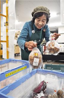 コンテナに野菜を詰める生産者の市川さん