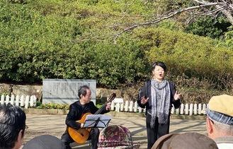 詩碑前で歌う北村さん(右)