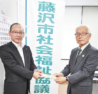 寄付金を手渡した富田さん(左)
