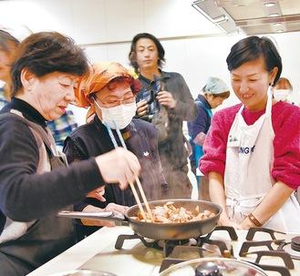 調理をする参加者と講師の馬田さん(右)