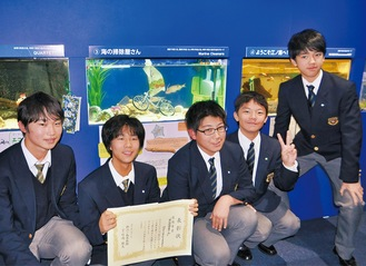 優秀賞の関東学院六浦中学高校生物部の生徒と水槽