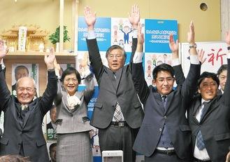 当選確実の一方を受け、支援者と万歳する鈴木氏(中央)