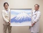 常田康夫院長に絵を手渡す内山さん(左)
