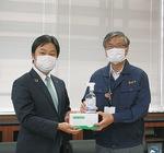 マスクを渡す野村理事長(左)