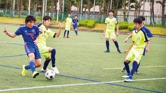 秋葉台球技場で開かれたサッカーの交流戦でボールを奪い合う選手ら