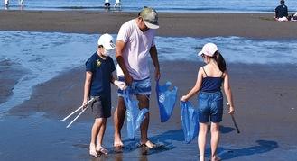 家族で海岸清掃する様子