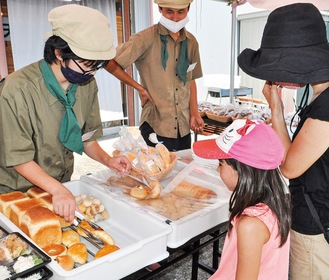 丁寧な接客でパンを販売する