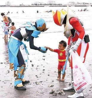 海岸でヒーローとごみを拾う参加者