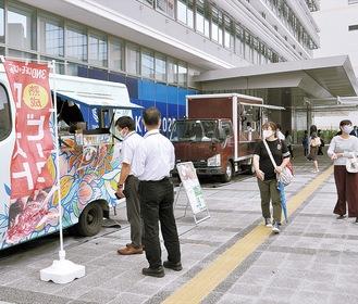 昼食を買い求める客で賑わう市庁舎西側広場(=23日)