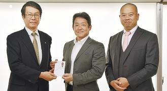 寄付を手渡す櫻井代表(右)と秋間代表(=20日、櫻井興業事務所)