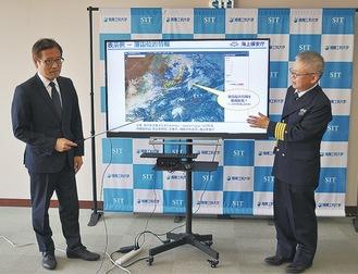 システムを紹介する成田教授(左)