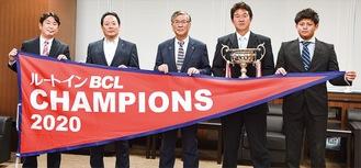 チャンピオンフラッグを持つ鈴木市長(真ん中)と鈴木監督(右から2番目)