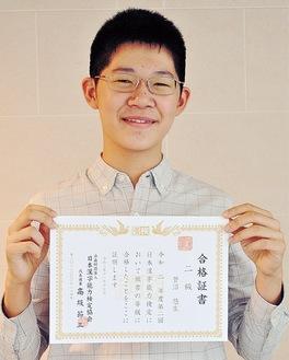 合格証書を手に笑顔を見せる菅沼君