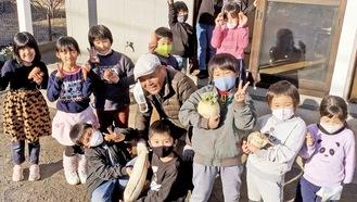 野菜を持った子どもたちに囲まれる椎野さん(中央)