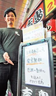「定食無料」の看板を店頭に掲げる店長の永田さん