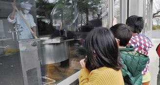 外から有川さんの調理風景を見る児童たち