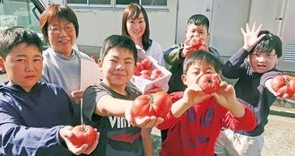 関戸さん(後列左)の作ったトマトを持つ中里小の児童