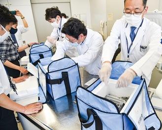 保冷バッグにワクチンを小分けする薬剤師