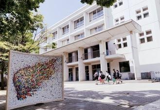 100周年記念事業の一環で寄贈された記念モニュメントと校舎(=4月25日)