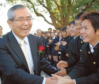 母校の湘南高校で在校生と握手を交わす根岸さん(左)(=2010年11月、鵠沼神明)