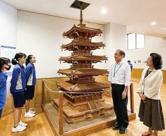 塔を前に生徒や内田誠一校長と談笑する麗子さん(右)