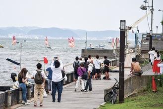 江の島の岸壁から競技を観戦する人々