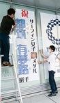 朗報を受け、手作りの懸垂幕を設置する市職員