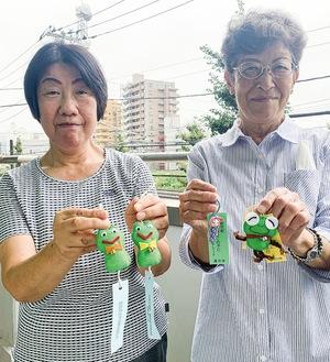 「無事にカエル」と「身を守るミノムシ」を持ちほほ笑む古川会長(左)と石川会長