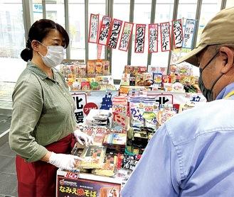 来店者に商品を紹介する杉原さん(左)(=9日、藤沢商工会館ミナパーク)
