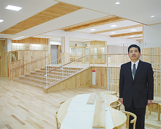 「スペースがゆったりとしています」と山田校長(職員室前の「相談コーナー」で)。この机は校内にあったイチョウの木を使用している