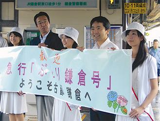 乗客をホームで迎える松尾市長(右から2番目)とミス鎌倉ら。観光パンフレットも配られた