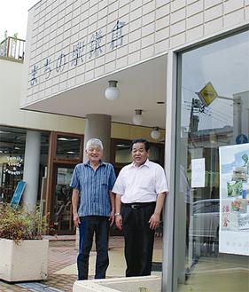 堀理事長(右)と菊一駅長。駅の前で