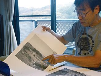 皆吉さんの写真を説明する島村さん。写真はすべて「6×6(ロクロク)」サイズのフィルムで。複写しA3用紙に印刷して展示する