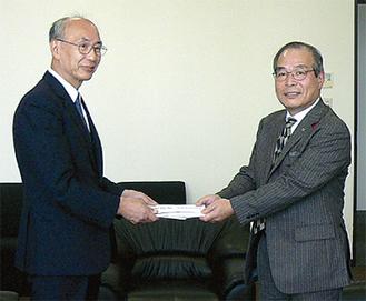 上遠野直人専務理事に奴田会長(右)が義援金を手渡した(今月4日)