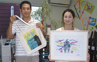 作品を手にする岩立代表(左)と下山田さん