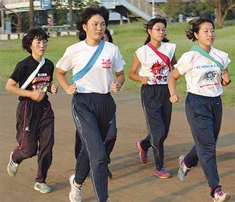 ウォーミングアップで走りこみをする同部員。青いたすきを掛けているのが森本さん=21日