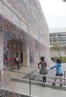 2万4000本のハンガーで作った壁が、昇降口の壁を埋め尽くした=30日