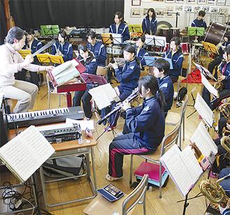 浅野教諭(左)の指揮に合わせて全体練習に取り組む生徒=3月9日、腰越中学校