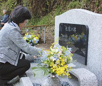 遺骨を埋葬後、花を手向ける同法人関係者=4月5日、光則寺