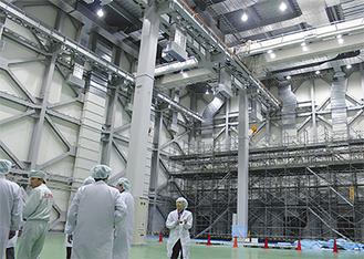 衛星の組立などを行う新生産棟で説明を聴く報道陣=12日