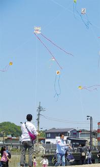「くまもん」などが描かれた手作り凧が空を彩る=提供