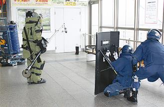 「マジックハンド」と呼ばれる器具で袋を処理する機動隊員=16日
